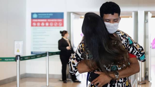 A man wearing a face mask hugs a woman amid the coronavirus disease (COVID-19) at Viracopos International Airport, in Campinas