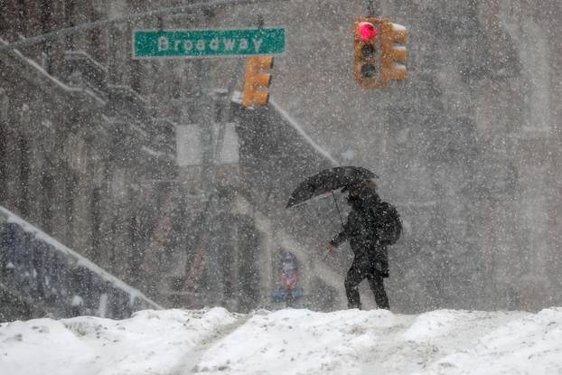 Woman walks in heavy falling snow during a winter storm in New York