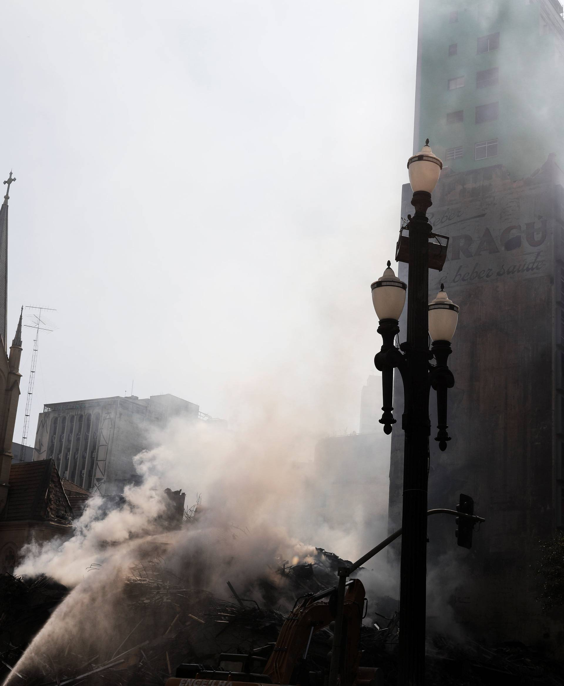 Firefighters try to extinguish the fire of a building that caught fire and collapsed in the center of Sao Paulo