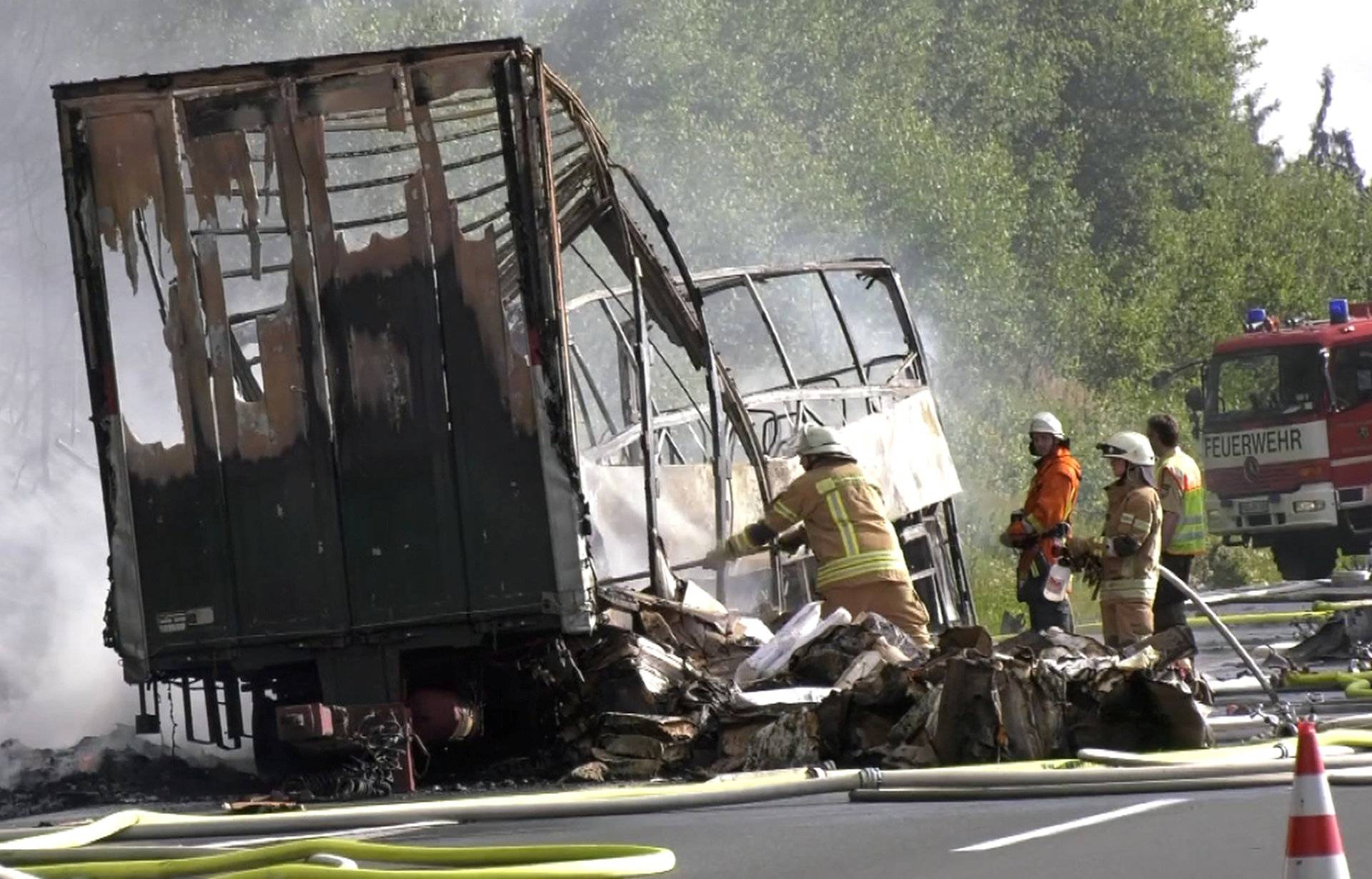 Firefighters walk at the site where a coach burst into flames after colliding with a lorry on a motorway near Muenchberg