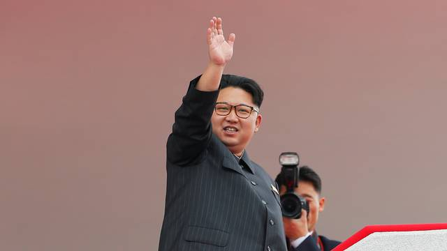North Korean leader Kim Jong Un waves to the crowd as he presides over a mass rally and parade in Pyongyang