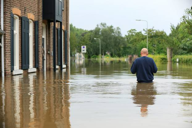 A person wades through water during a flood in Guelle