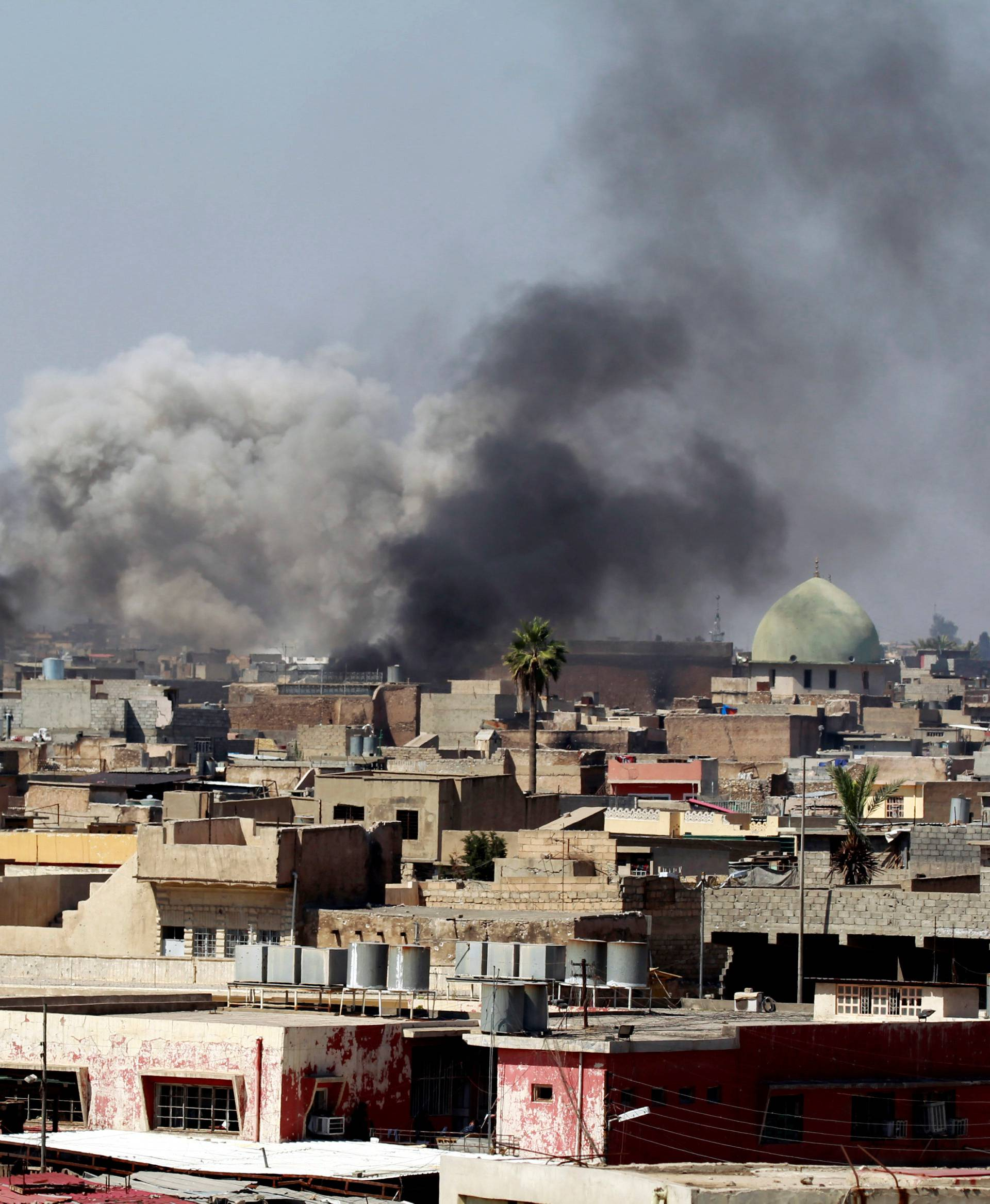 Smoke rises over the city during clashes between Iraqi forces and Islamic State militants, in Mosul