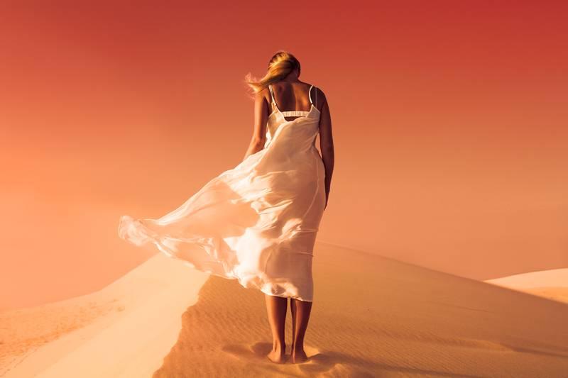 Woman in fluttering dress. Desert and sand dunes. Red sky. Mars.
