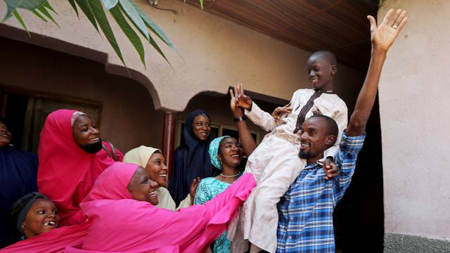 Muhammed Bello, a rescued student, is carried by his father as his relatives celebrate after he retuned home in Kankara