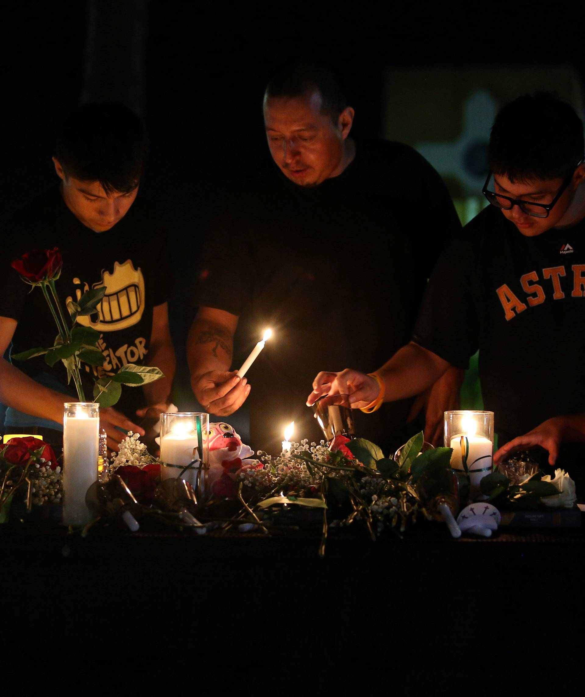 Attendees light a candle to pay their respects to the victims of a shooting at Santa Fe High School that left several dead and injured in Santa Fe, Texas