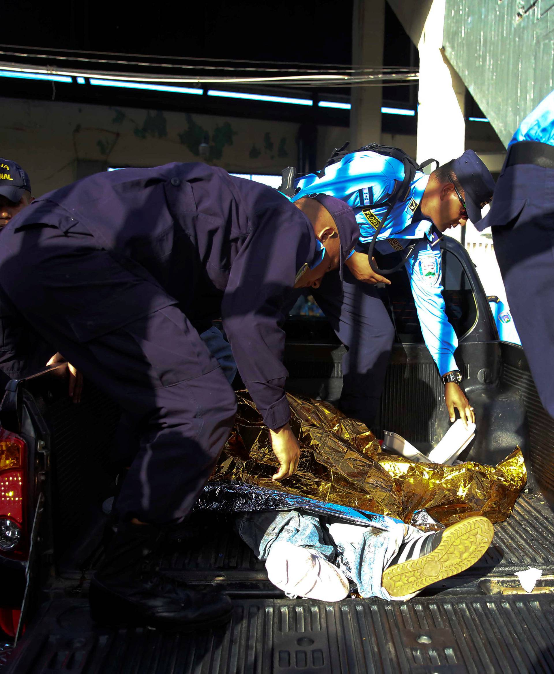 Members of the national police stand next to a dead body after an stampede at the National Stadium in Tegucigalpa