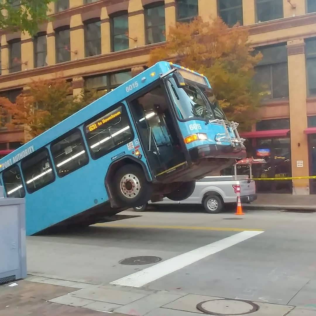 Front of a public bus sticks out of a sinkhole on 10th and Penn Avenue in Pittsburgh