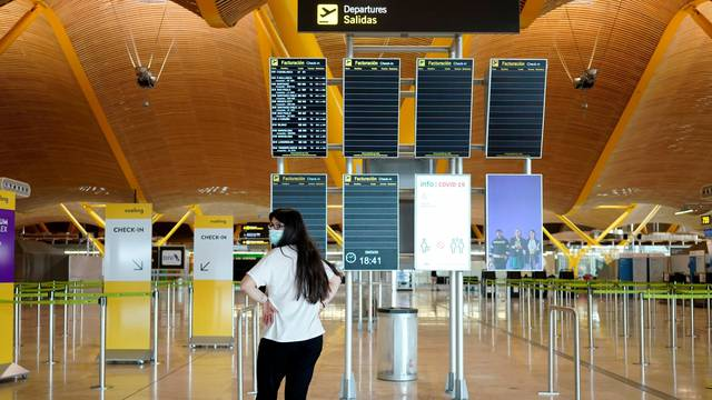 A woman wearing a protective mask stands in front of flight screens at the almost empty Madrid's Adolfo Suarez Barajas Airport