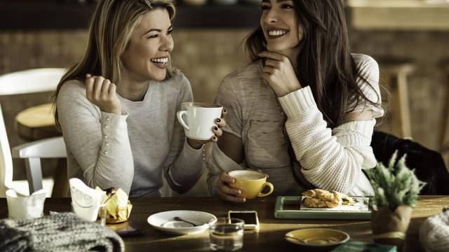 Two cheerful women having fun during coffee time in a cafe.