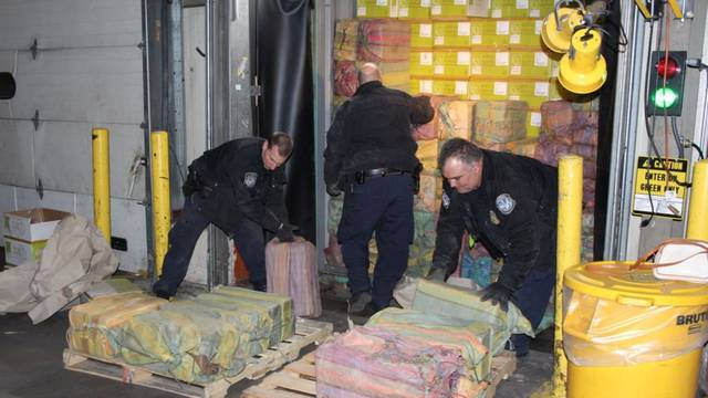 Law enforcement officers unload cocaine seized at the Port of New York/Newark