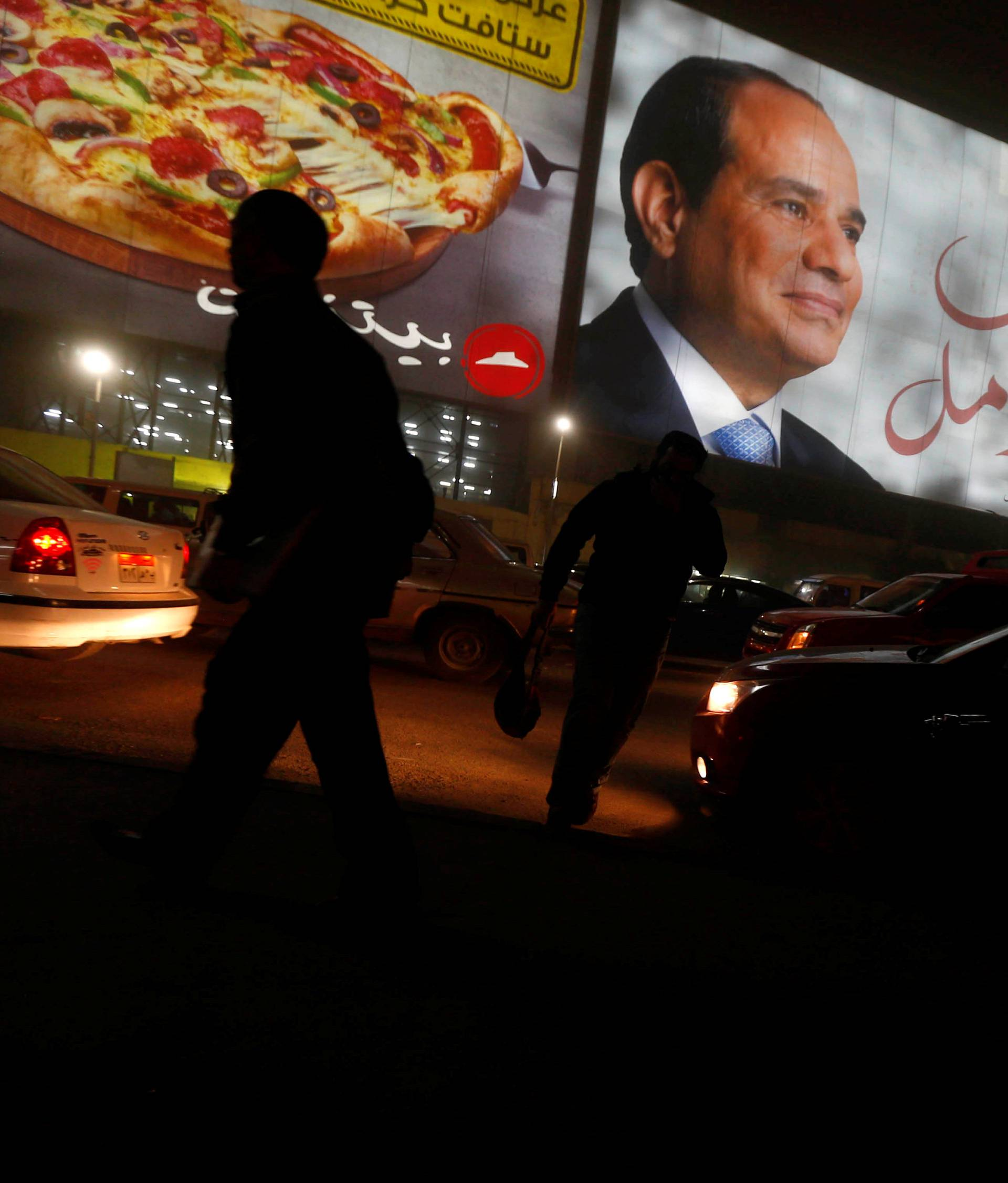 People walk near a billboard showing a picture of Egyptian President Abdel Fattah al-Sisi during the presidential election in Cairo