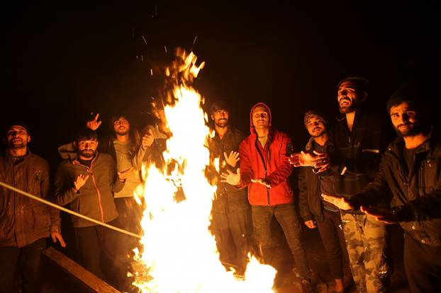 """Migrants warm up around a fire at camp """"Lipa"""" after it was closed, in Bihac"""