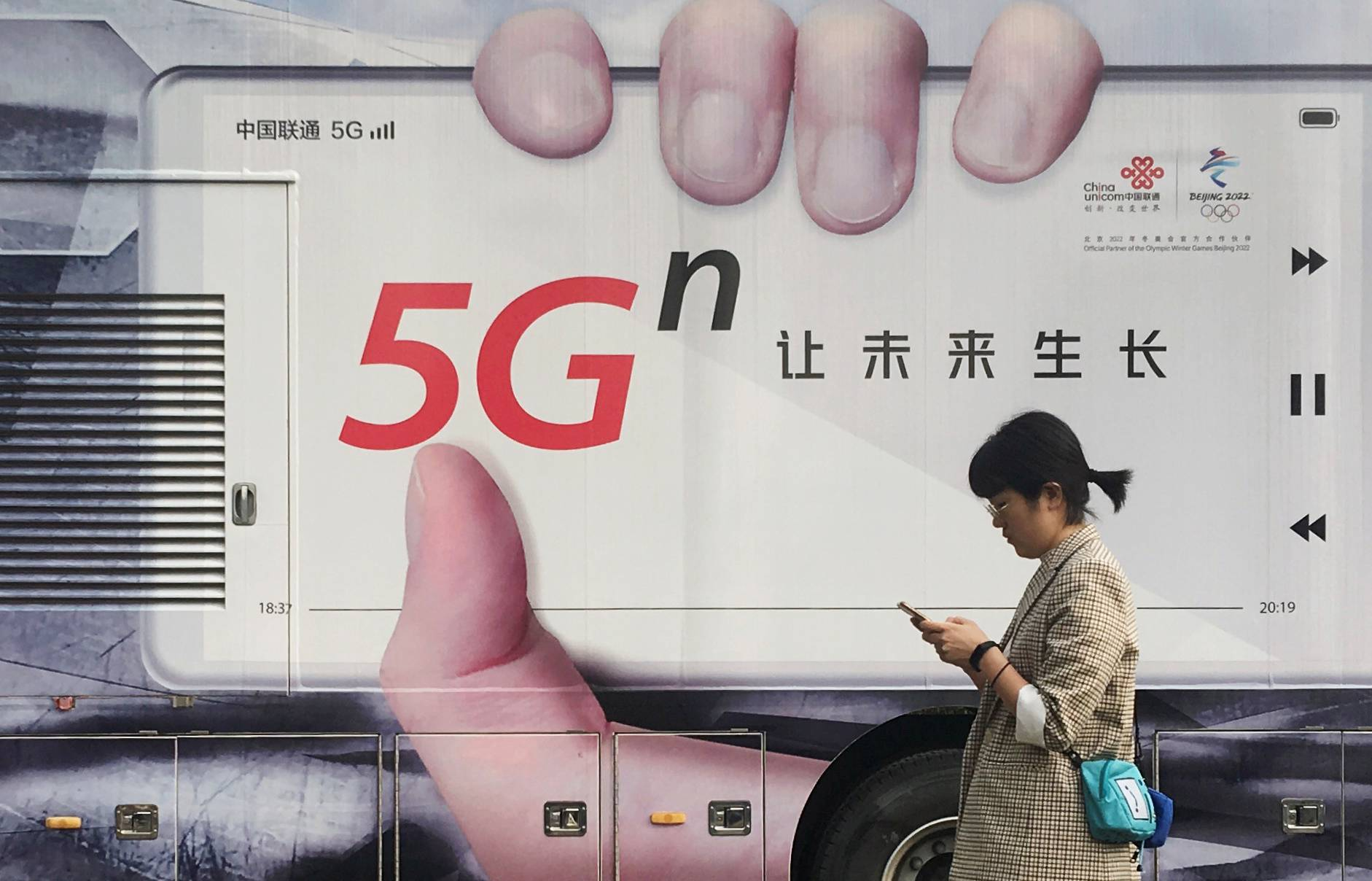 Woman using her mobile phone walks past a vehicle covered in a China Unicom 5G advertisement in Beijing