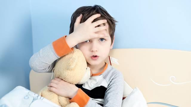 Sick little boy hugs his teddy bear in bed
