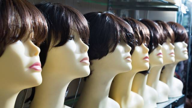 Mannequins with brown-haired and brunet style wigs on shelves