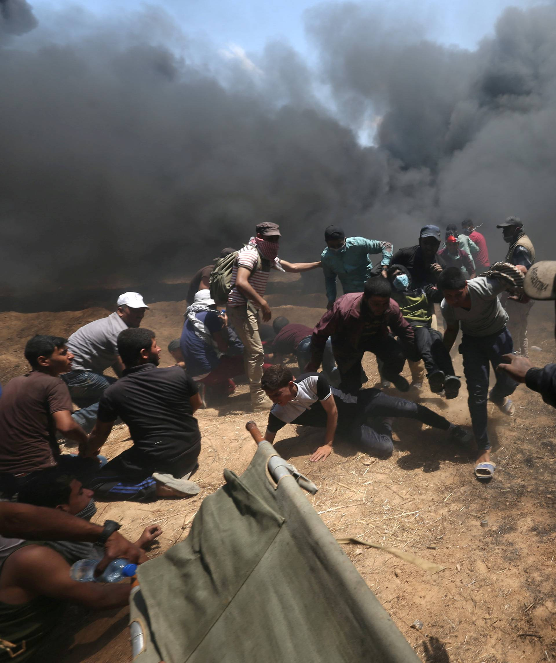 Wounded Palestinian demonstrator is evacuated as others take cover from Israeli fire and tear gas during a protest against U.S. embassy move to Jerusalem and ahead of the 70th anniversary of Nakba, at the Israel-Gaza border in the southern Gaza Strip