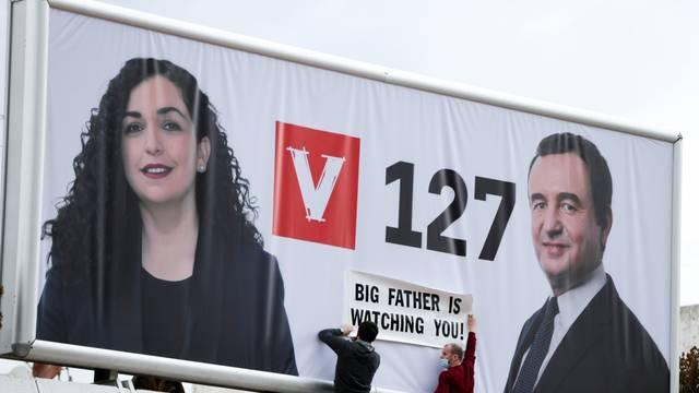 People place a slogan on the poster of Albin Kurti, leader of the Self-Determination movement (Vetevendosje), and the Kosovo's acting president, Vjosa Osmani, in Pristina