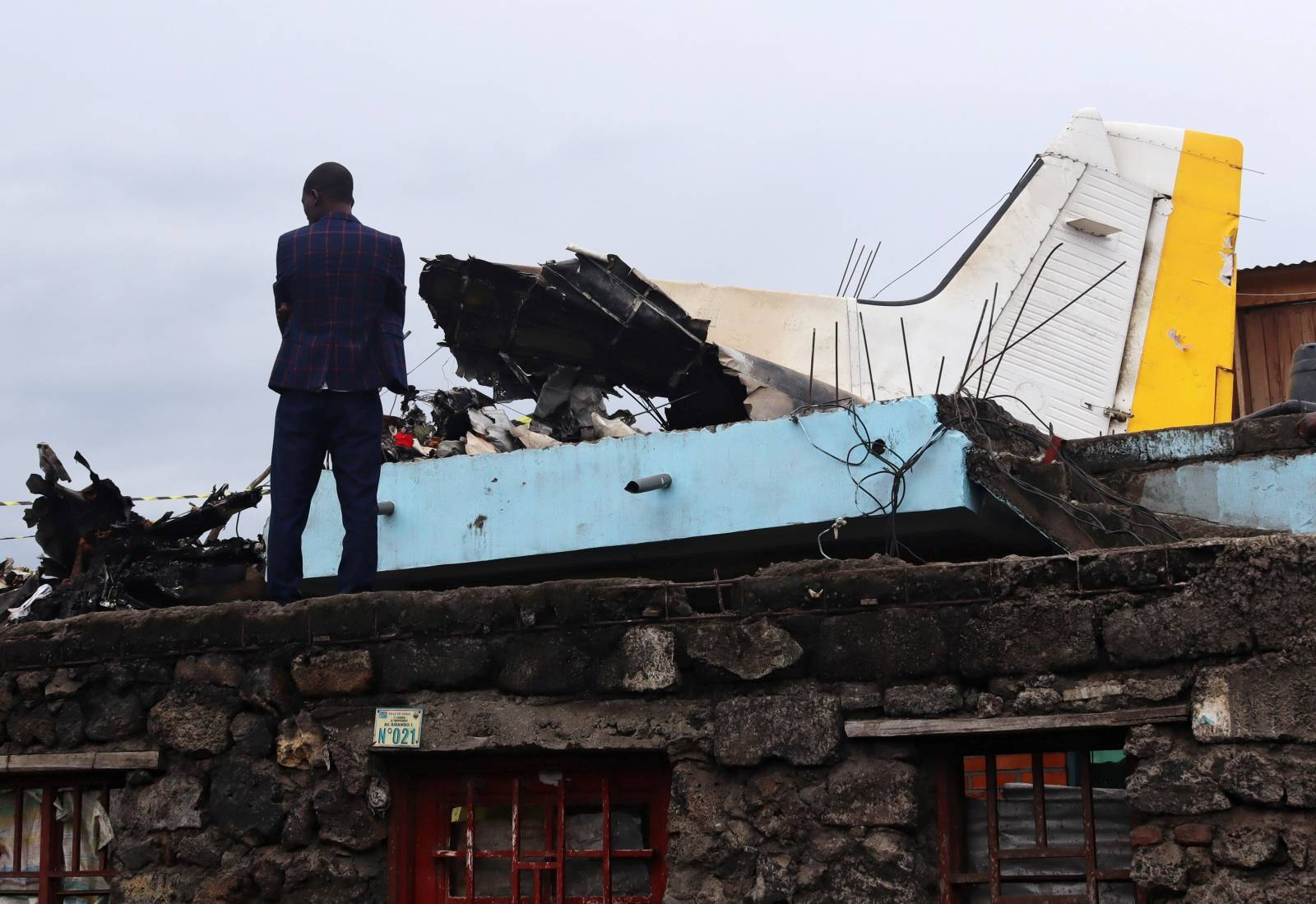 A man stands at the site where a plane Dornier 228-200 plane operated by local company Busy Bee crashed into a densely populated neighborhood in Goma