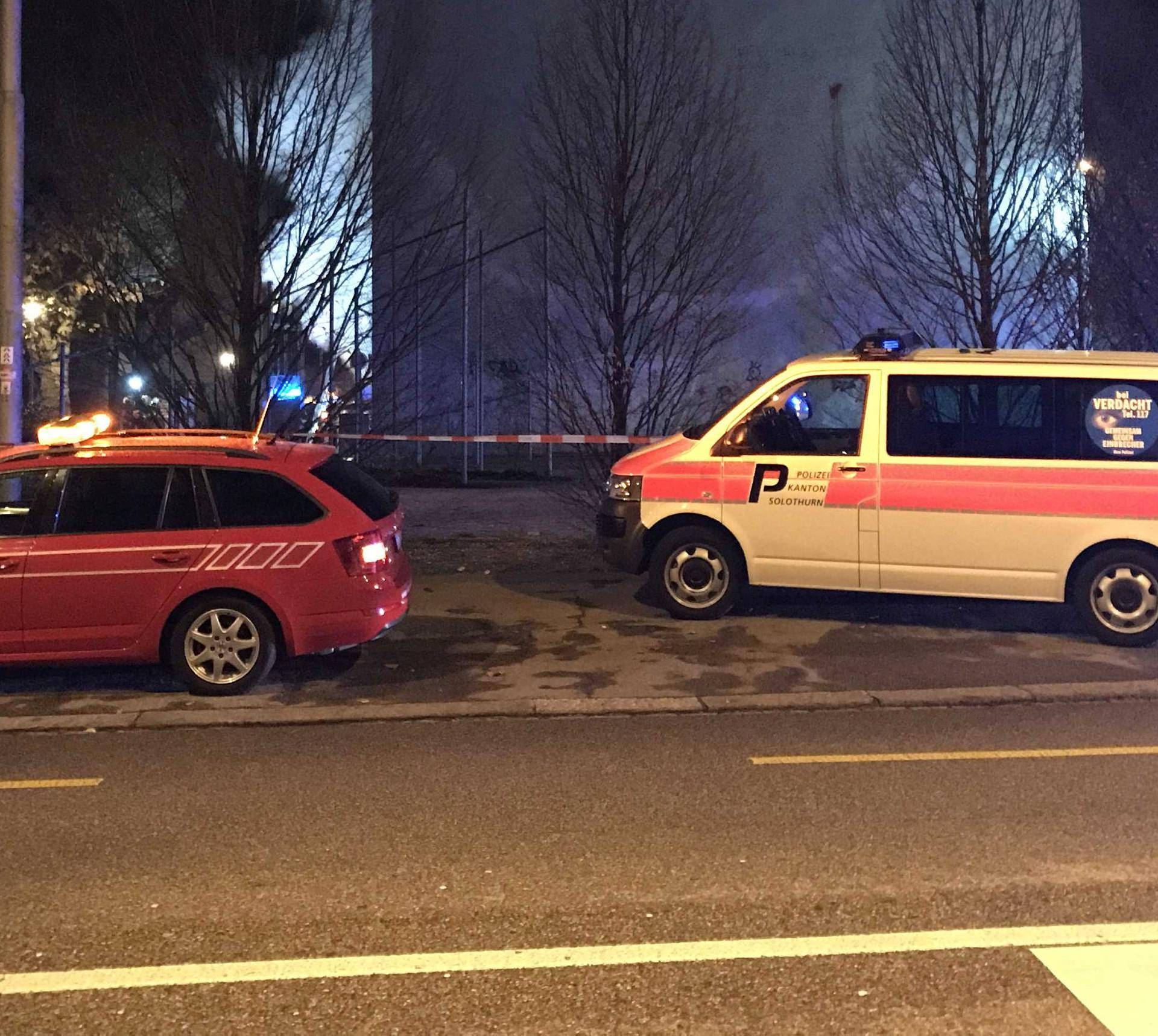 Operational vehicles of police and firefighters are seen in front of a house where six people were killed in an apartment fire early on Monday morning, police said in Solothurn