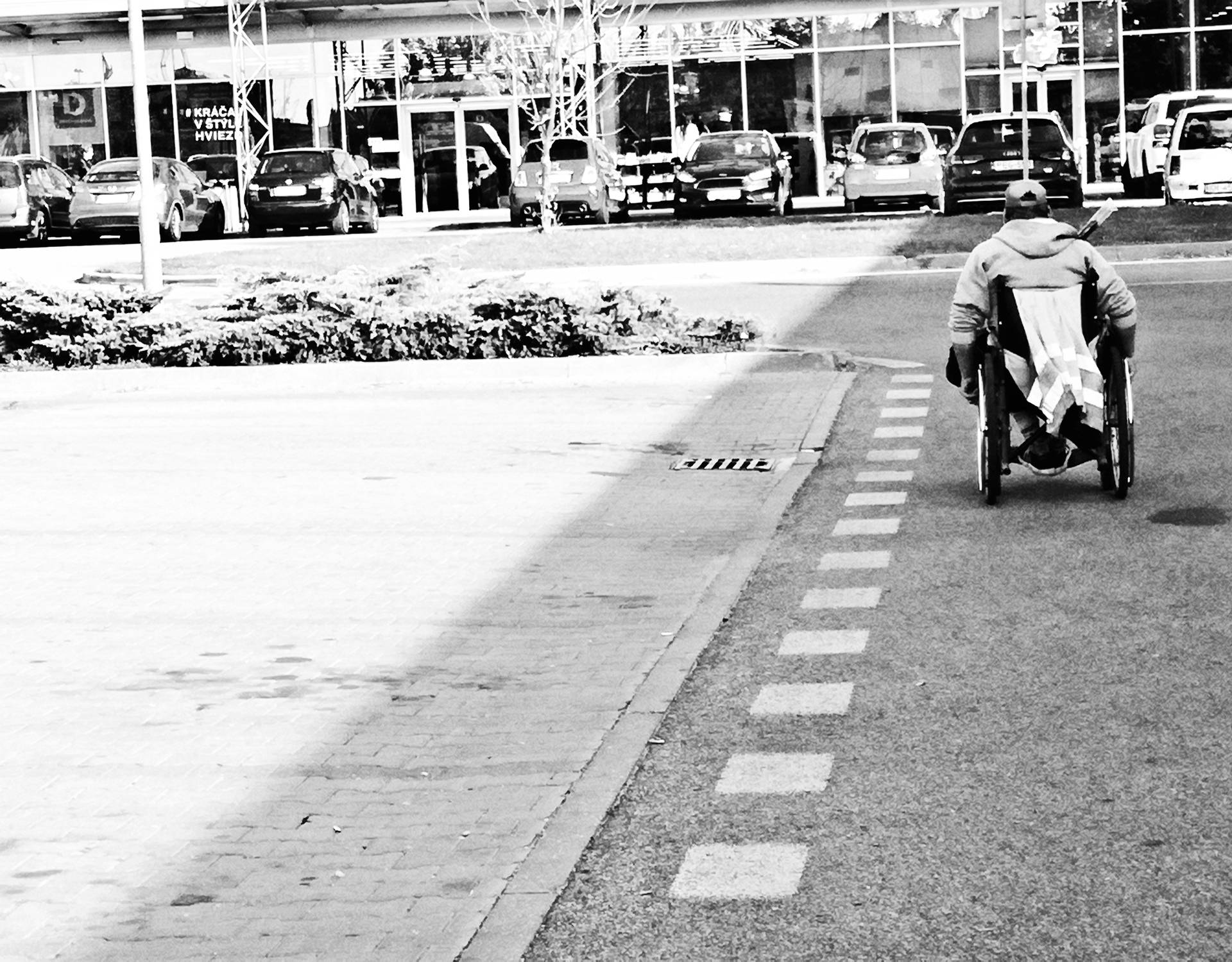 A man using wheel chair on an empty road in Stuttgart - Germany. Black and white image
