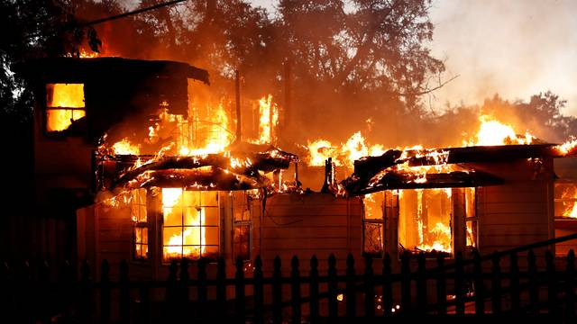 A burning house damaged by the Clayton Fire is seen near Lower Lake in California