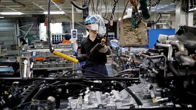 FILE PHOTO: An employee wearing a protective face mask and face guard works on the automobile assembly line at the factory of Mitsubishi Fuso Truck and Bus Corp in Kawasaki