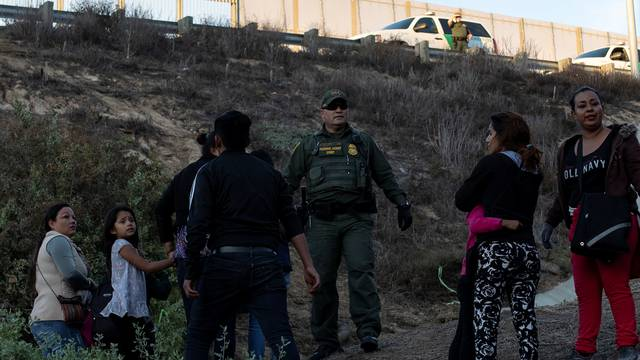 A U.S. Customs and Border Protection (CBP) official stands among migrants photographed through the border wall in Tijuana