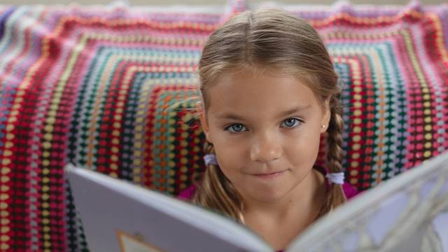 Font view of cute Caucasian girl looking at camera while reading a book on sofa in a comfortable home