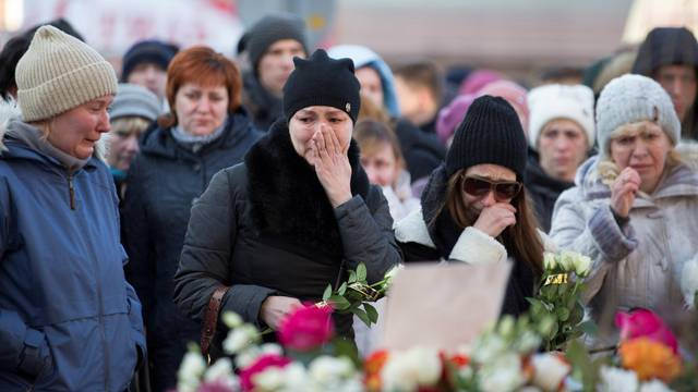 People mourn the victims of a shopping mall fire at a makeshift memorial in the Siberian city of Kemerovo