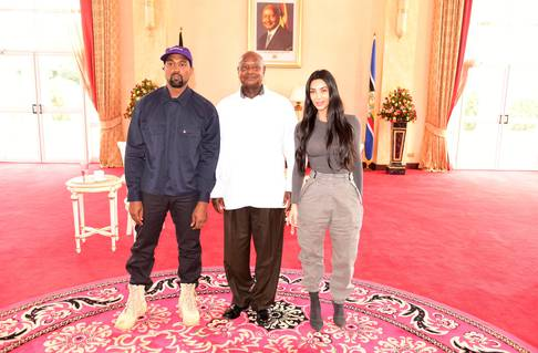 Rapper Kanye West and Kim Kardashian pose for a photograph with Uganda