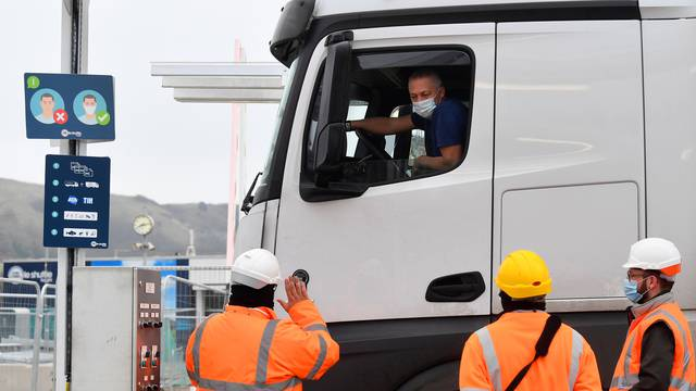 Lorry drivers show documentation as they arrive at Eurotunnel to travel to France, Folkestone, Britain
