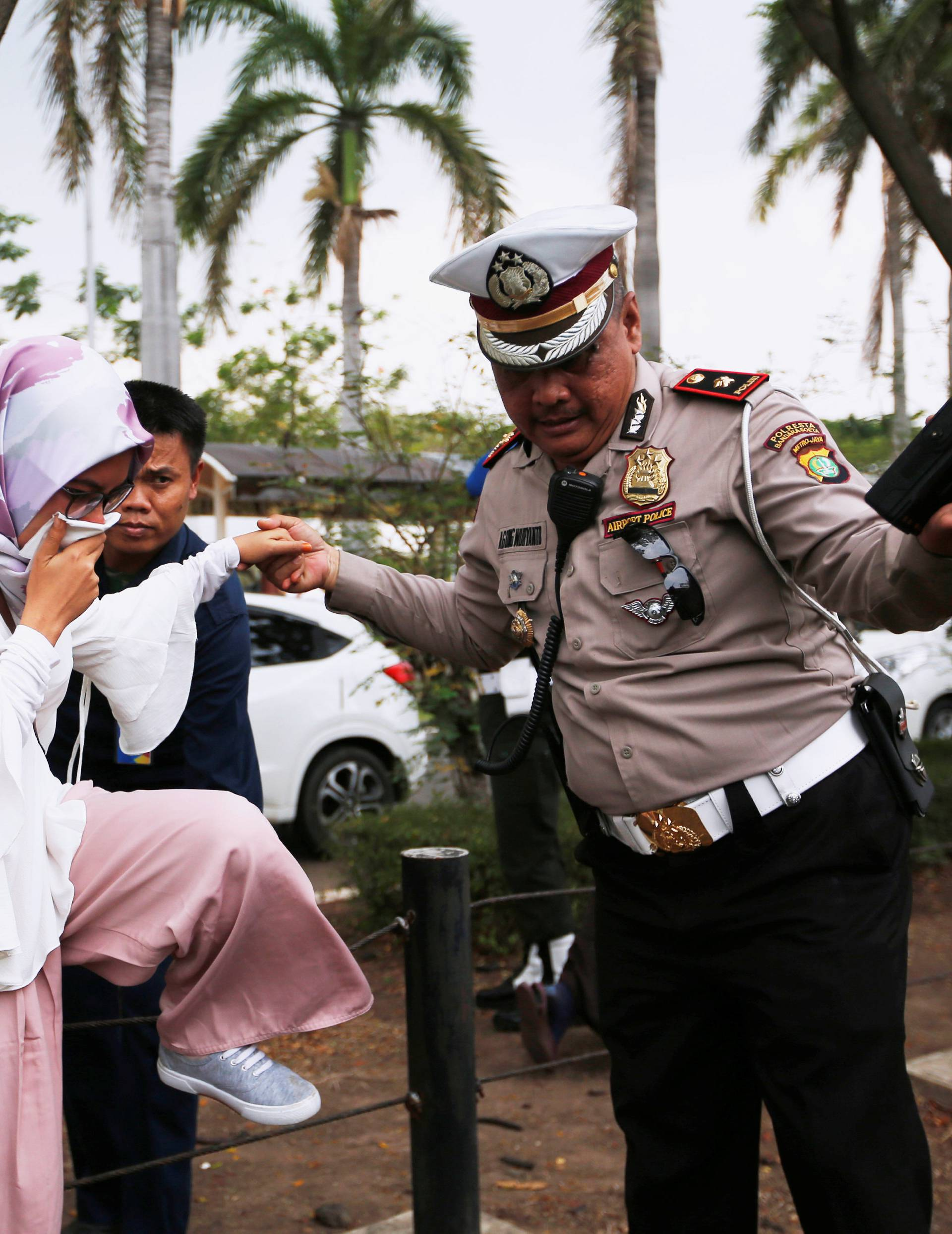 A policeman helps a woman who is a relative of a passenger of Lion Air flight JT610 that crashed into the sea, as she arrives at a crisis center at Soekarno Hatta International airport near Jakarta