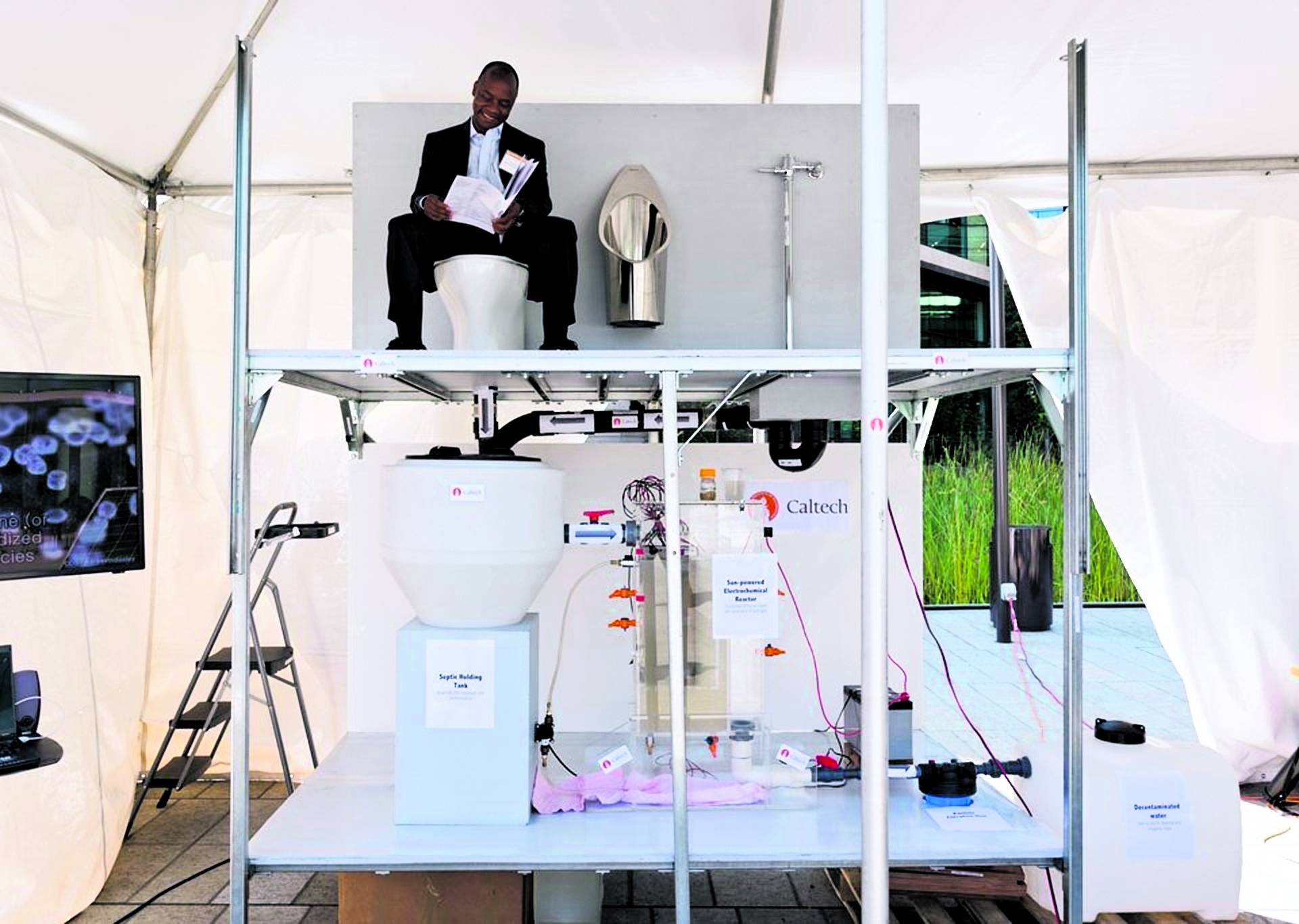 Doulaye Kone sits on the toilet at the winning prototype, a system designed by researchers from California Institute of Technology (exhibit 30) at the Reinvent the Toilet Fair in Seattle on August 12, 2012. Their model is a solar-powered toilet that gener