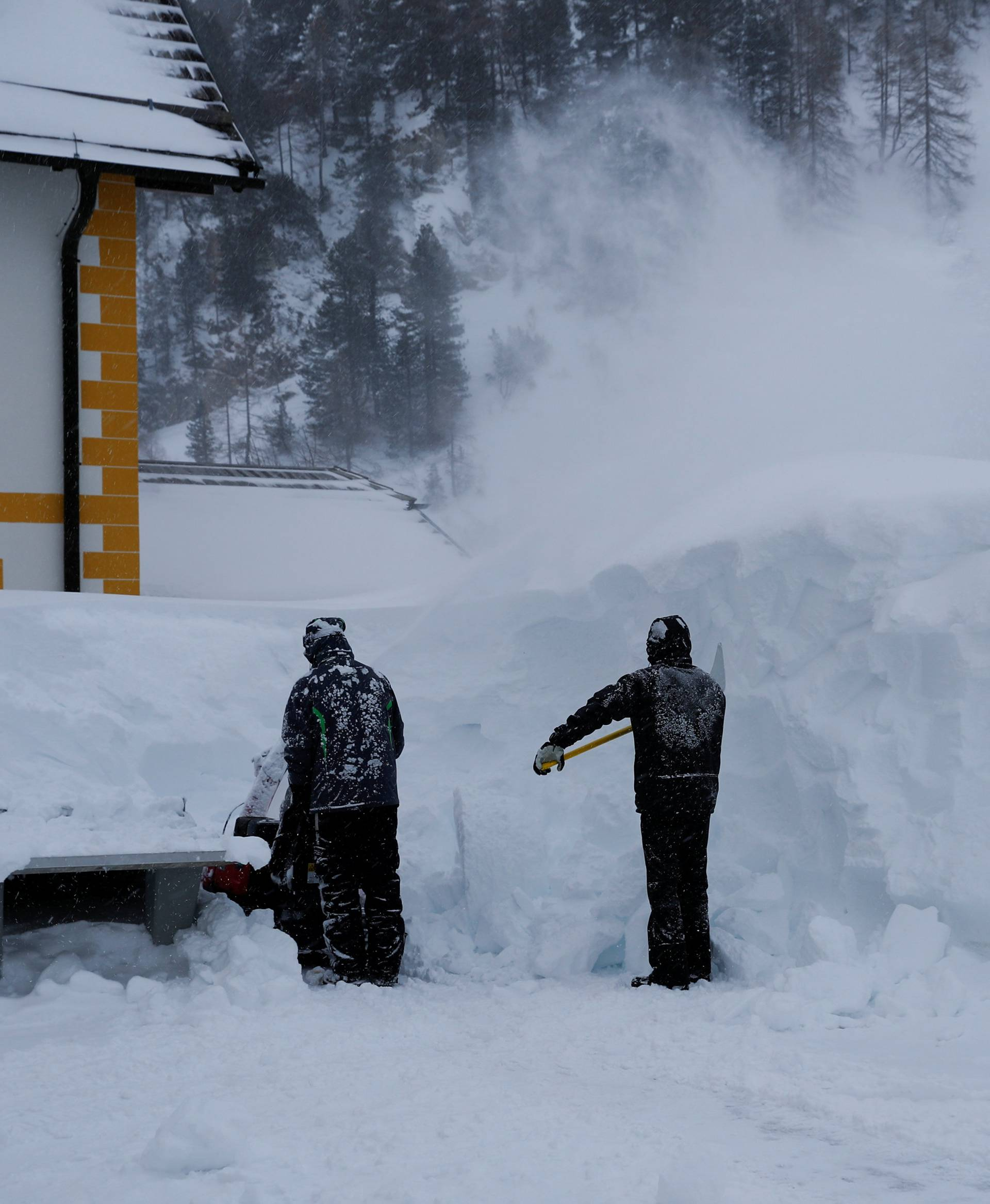 FILE PHOTO: Two workers remove snow after a blizzard in the Austrian Alpine ski resort of Obertauern
