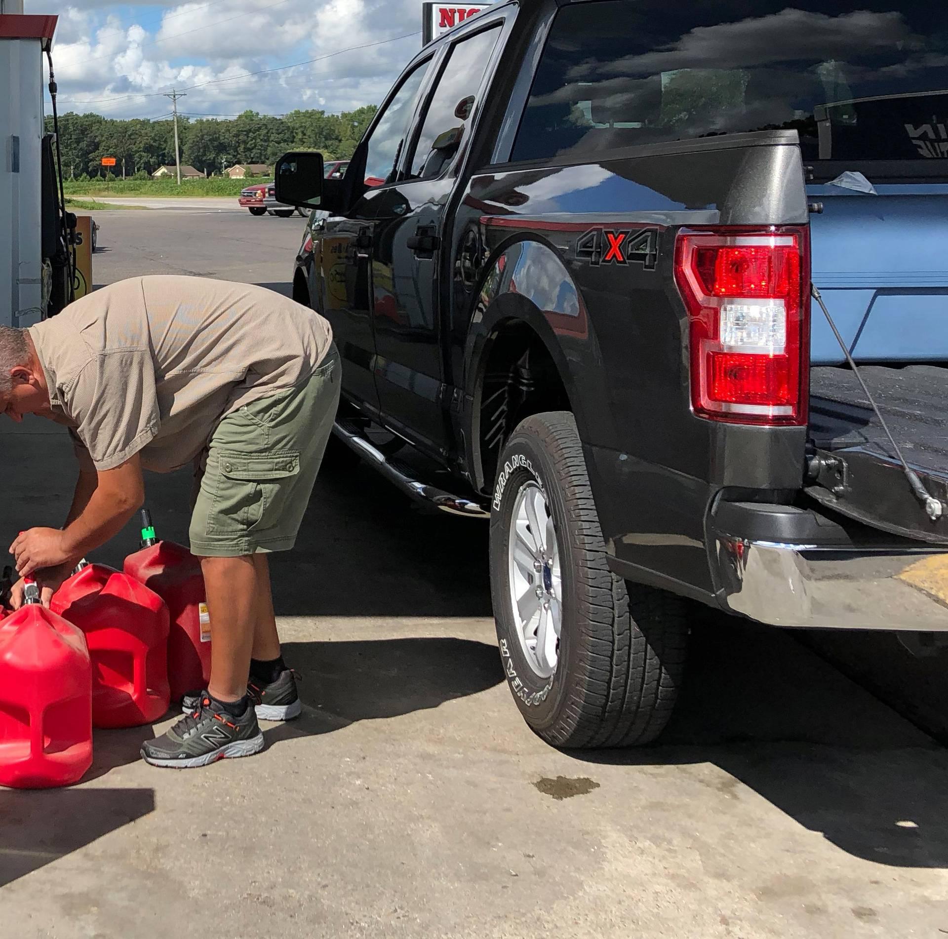 Trent Bullard fills gas containers for his generator ahead of Hurricane Florence in Pembroke North Carolina