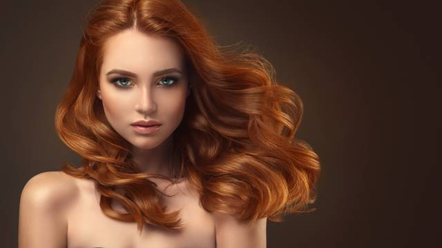 Red haired woman with voluminous, shiny and curly hairstyle.Flying hair.