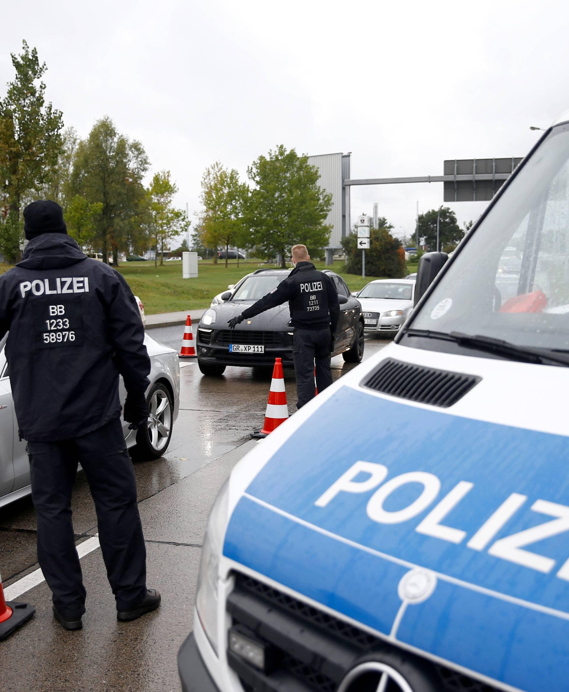 German policemen check cars on the entrance to Berlin-Schoenefeld airport, in Schoenefeld