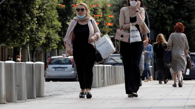 FILE PHOTO: Women wearing masks walk on a street after Prime Minister Dusko Markovic declared the country the coronavirus disease (COVID-19)-free in Podgorica