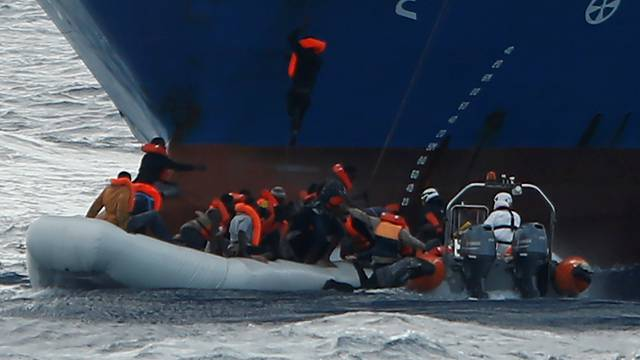 Migrants in a rubber dinghy fall into the sea alongside a RHIB of the Malta-based NGO Migrant Offshore Aid Station, as a migrant climbs to the anchor of the Panama-registered ship Tuna 1 and one hangs onto its bow