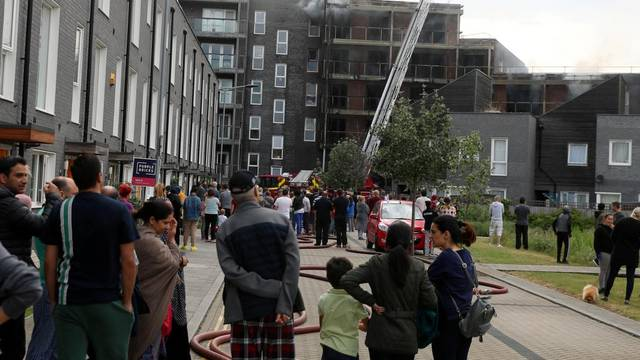 Firefighters work on top of a block of flats after a fire broke out in Barking
