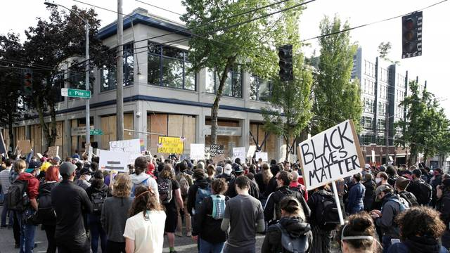 Protesters demonstrate outside the Seattle Police Department's East Precinct after the building was boarded up and vacated in Seattle