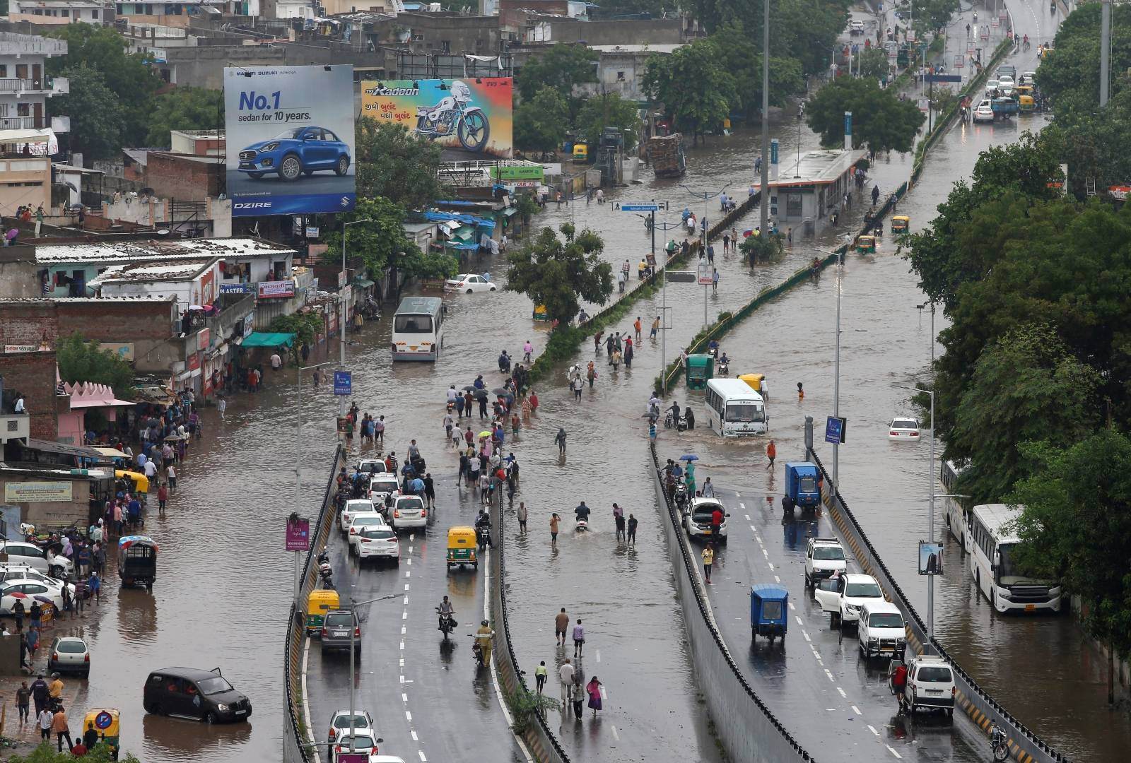 People commute through water-logged roads after heavy rains in Ahmedabad
