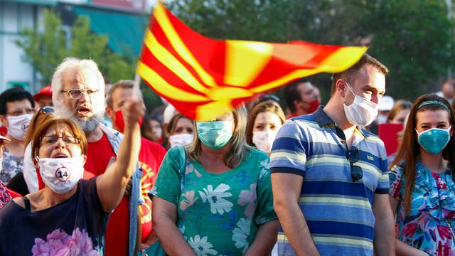 A supporter of Macedonia's nationalist opposition party VMRO-DPMNE leader Hristijan Mickoski waves a party flag during a gathering, in Skopje