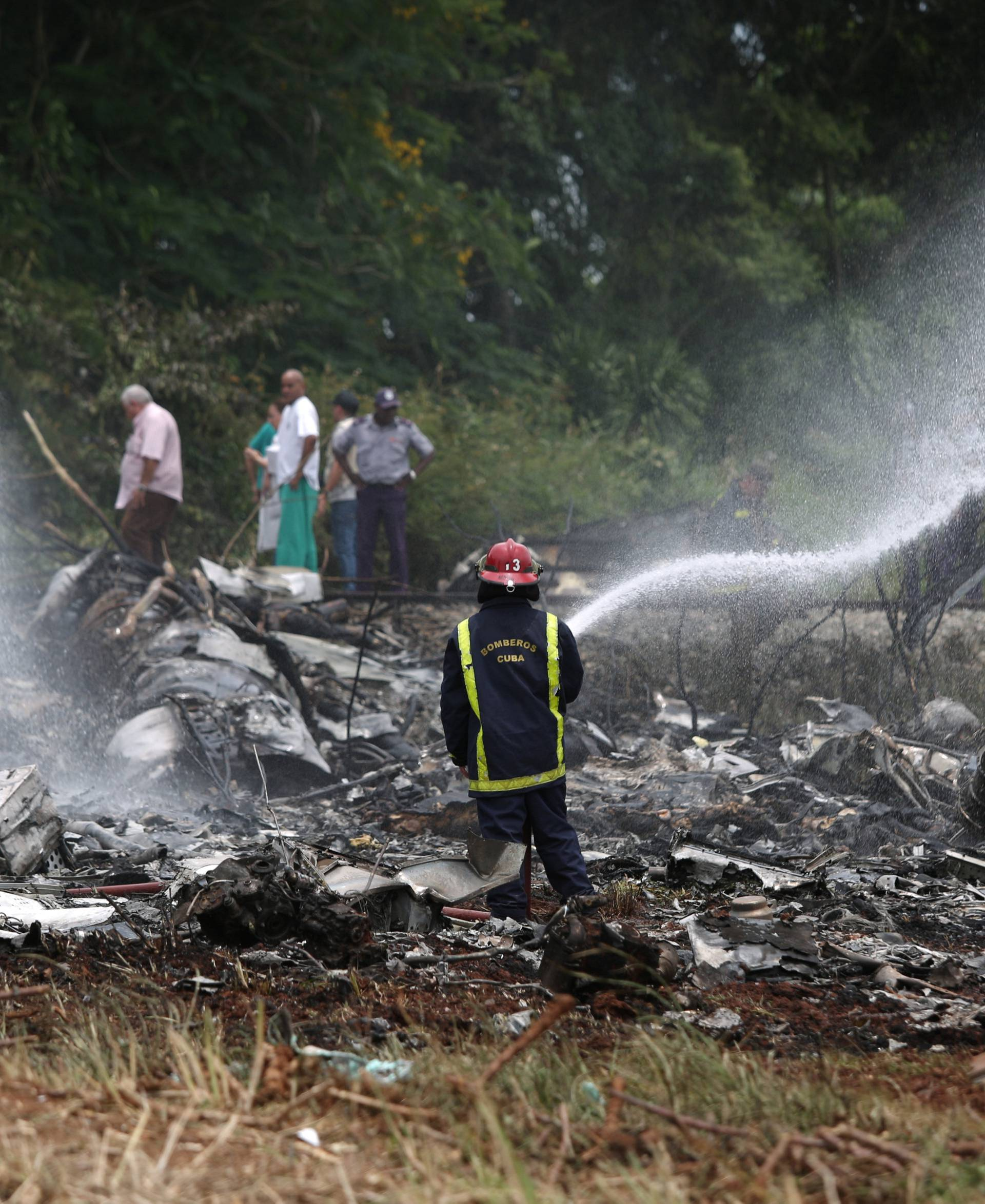 A fire fighter works in the wreckage of a Boeing 737 plane that crashed  in the agricultural area of Boyeros, some 20 km (12 miles) south of Havana on Friday shortly after taking off from Havana's main airport in Cuba