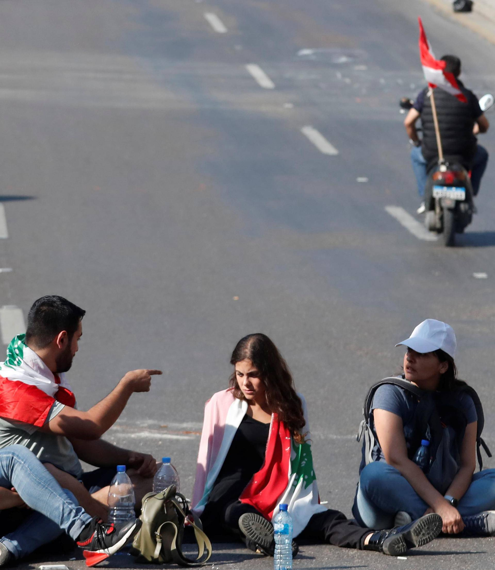 Protesters sit on the road during a road block in Beirut