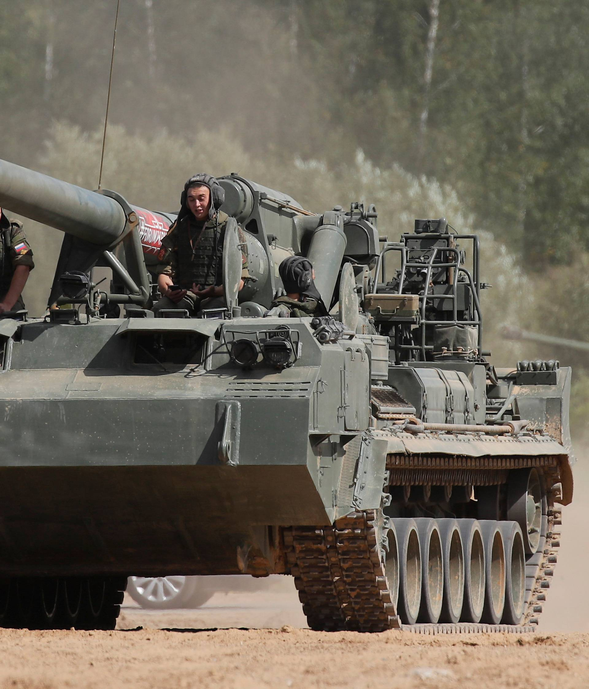 """Russian servicemen sit atop a 2S5 Giatsint-S self-propelled howitzer during the annual international military-technical forum """"ARMY"""" in Alabino"""