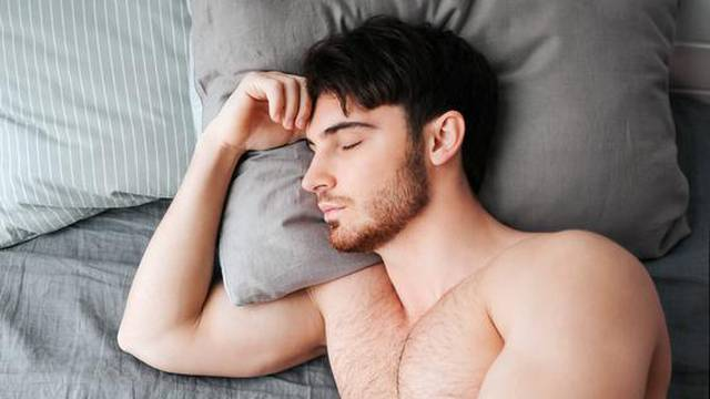 Single young muscular man sleeping in bed. He hold head on pillow. Young man is naked. Lower part of body covered with grey blanket.