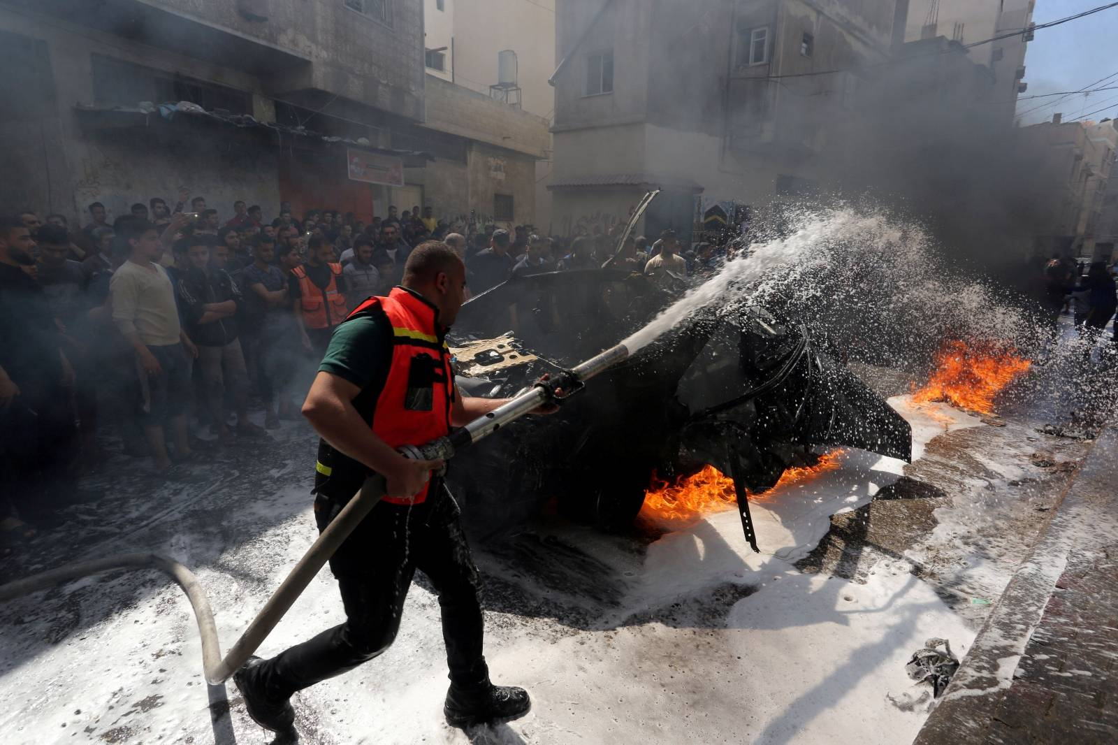 Member of Palestinian Civil Defence extinguishes a fire in the car of a Hamas commander who was killed in an Israeli air strike, in Gaza City