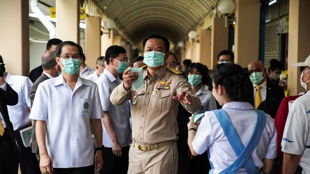 Anutin Charnvirakul, Thailand's Deputy Prime Minister and Minister of Public Health distributes protective face masks to people at a hospital before a news conference about the new coronavirus situation in Bangkok